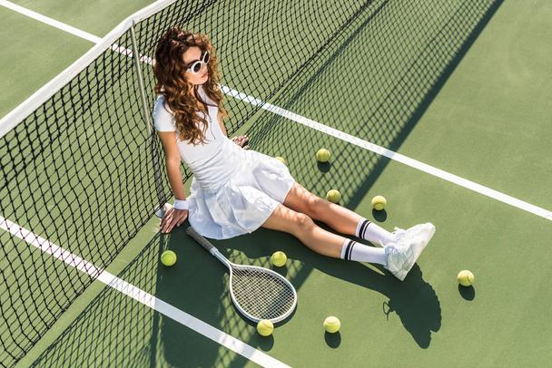 high angle view of young beautiful tennis player in white sportswear and sunglasses sitting at net with tennis equipment around on tennis court - Photo, Image