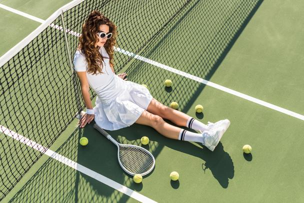 high angle view of stylish tennis player in white sportswear and sunglasses sitting at net with tennis equipment around on tennis court - Photo, Image