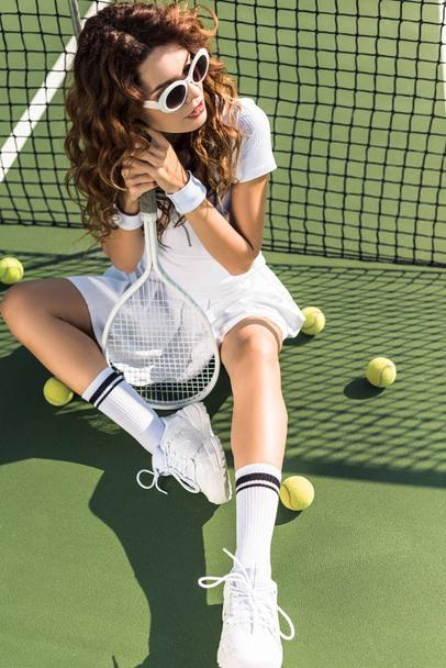 young beautiful sportswoman in sunglasses with tennis racket sitting at tennis net on tennis court - Photo, Image
