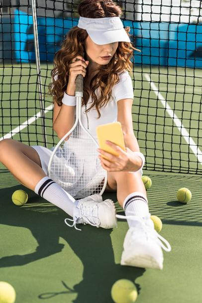 fashionable tennis player in white sportswear with equipment taking selfie on smartphone at net on tennis court - Photo, Image