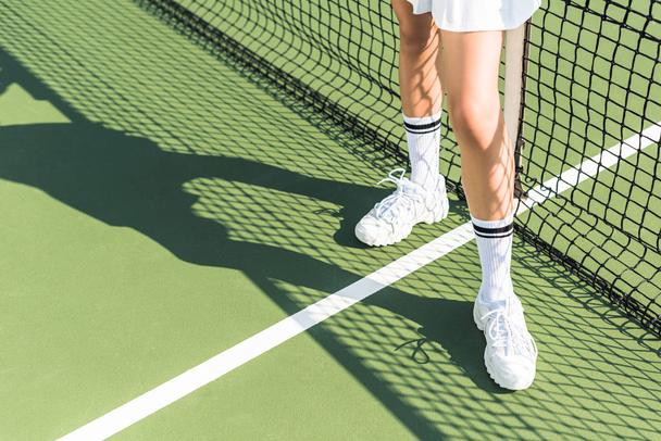 partial view of female tennis player standing near tennis net on court - Photo, Image