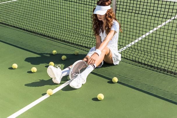 beautiful tennis player in white tennis uniform with racket sitting near tennis net on court with tennis balls around - Photo, Image