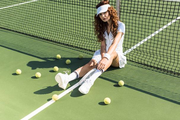 beautiful tennis player in stylish sportswear with racket sitting near tennis net on court with tennis balls around - Photo, Image