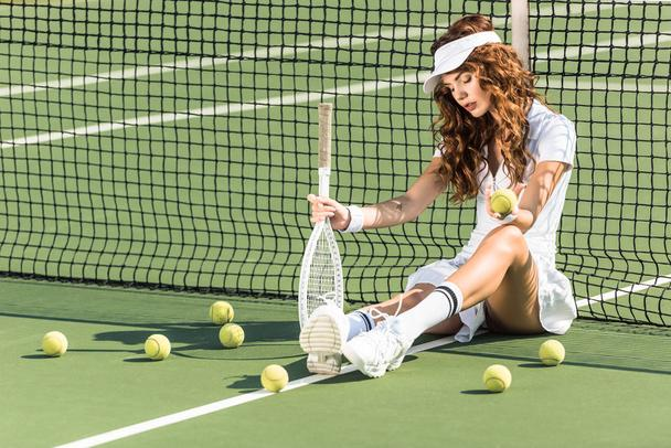 beautiful female tennis player with racket sitting near tennis net on court with tennis balls around - Photo, Image