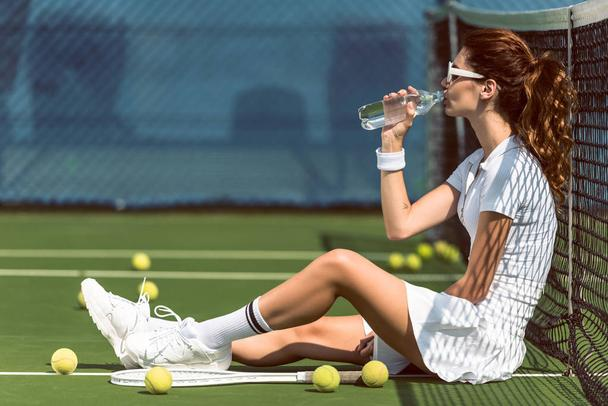side view of beautiful tennis player in white tennis uniform and sunglasses drinking water while resting on court with racket and balls - Photo, Image