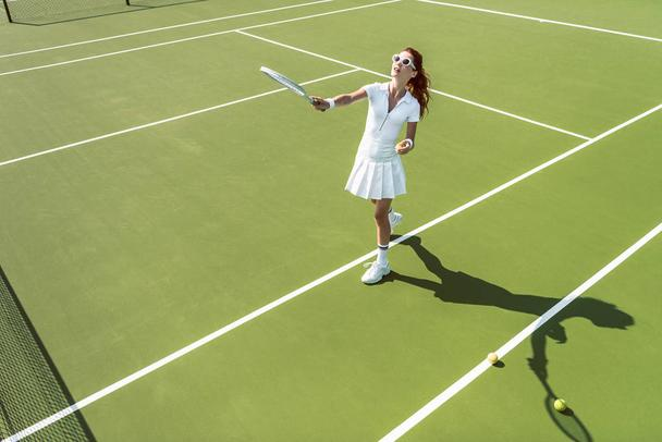 side view of young attractive woman in white tennis uniform playing tennis on court - Photo, Image