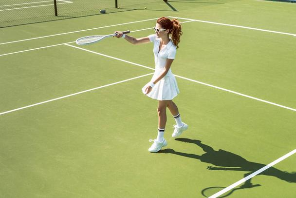 young female tennis player in sunglasses playing tennis on court - Photo, Image