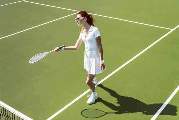 beautiful woman on white sportswear and sunglasses playing tennis on court - Photo, Image