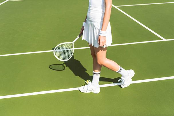 partial view of female tennis player in white sportswear with racket on tennis court - Photo, Image