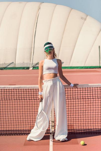 stylish woman in white clothing and cap with tennis racket posing at tennis net on court - Photo, Image