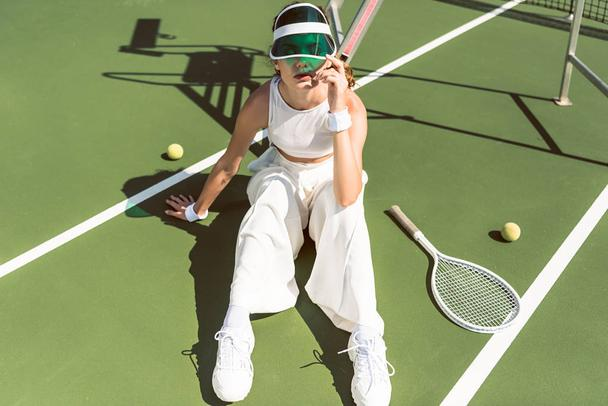 young woman in stylish white clothing and cap sitting on tennis court with racket and balls - Photo, Image