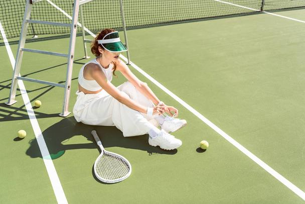 young woman in stylish white clothing and cap tying shoelaces on tennis court with racket and balls - Photo, Image