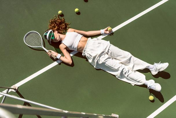 high angle view of stylish woman in white clothing and cap lying with racket lying on tennis court with racket - Photo, Image