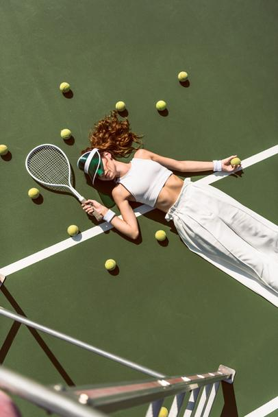 overhead view of stylish woman in white clothing and cap lying with racket lying on tennis court with racket - Photo, Image