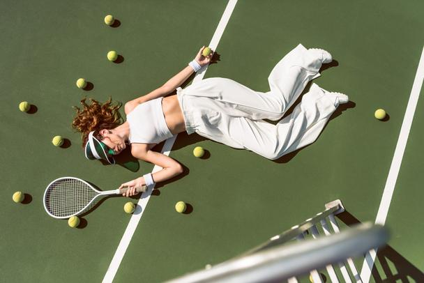 overhead view of attractive woman in white clothing and cap lying with racket lying on tennis court with racket - Photo, Image