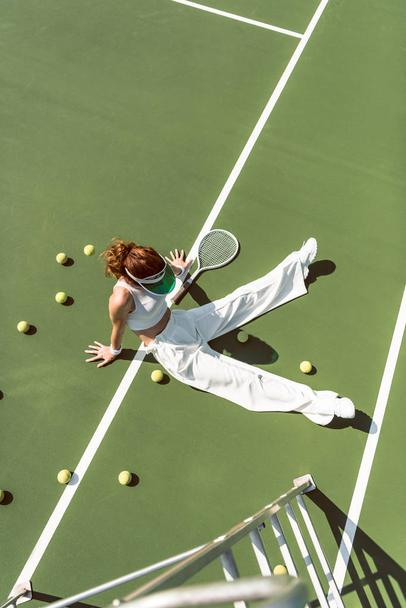 high angle view of beautiful woman in stylish white clothing sitting on tennis court with balls and racket around - Photo, Image