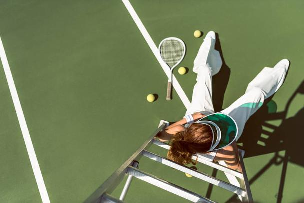 overhead view of woman in stylish white clothing and cap posing on referee chair on tennis court - Photo, Image