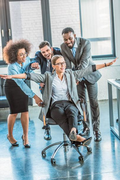 multicultural businesspeople having fun and racing colleague on chair in workspace - Photo, Image