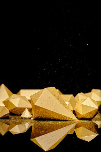 shiny glittering pieces of gold and golden dust reflected on black background  - Photo, Image