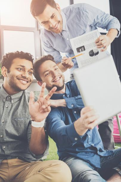 Smiling young businessmen using digital tablet and showing charts, business teamwork concept - Photo, Image