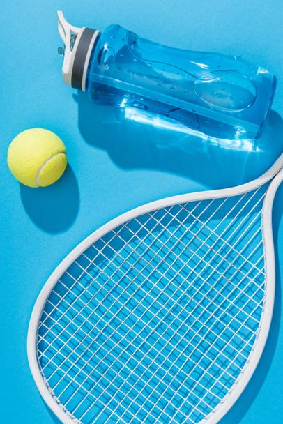 close up view of sportive water bottle and tennis equipment on blue backdrop - Photo, Image