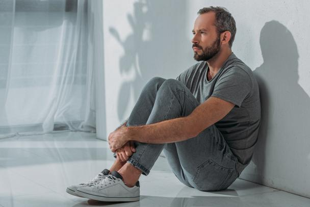 side view of sad bearded mid adult man sitting on floor and looking away - Photo, Image