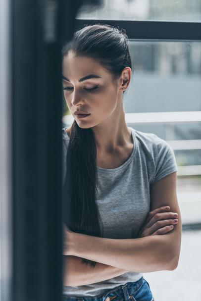 depressive young brunette woman standing with crossed arms near window - Photo, Image