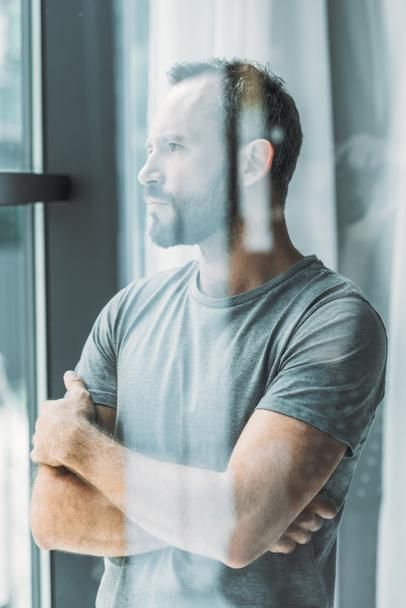 selective focus of bearded middle aged man standing with crossed arms and looking at window - Photo, Image