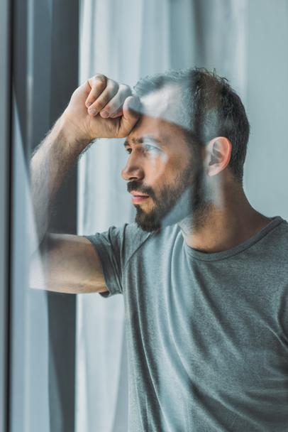 side view of sad bearded man looking at window - Photo, Image