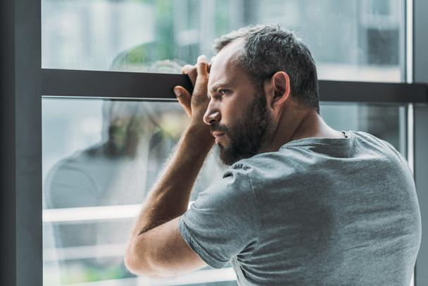 upset bearded man leaning at window and looking through it   - Photo, Image