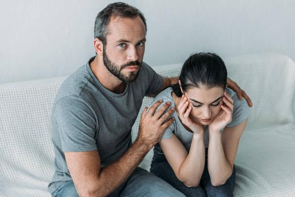 high angle view of bearded man supporting upset girlfriend and looking at camera - Photo, Image