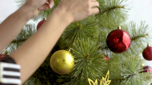 cropped view of woman decorating christmas tree with balls at home - Footage, Video