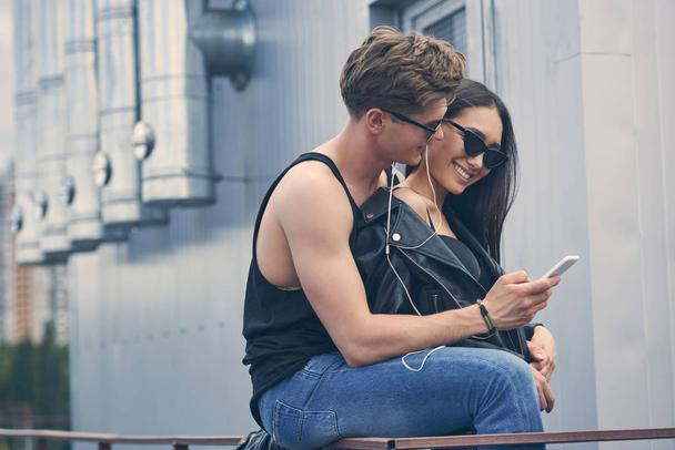 smiling interracial couple listening music with earphones and using smartphone - Photo, Image