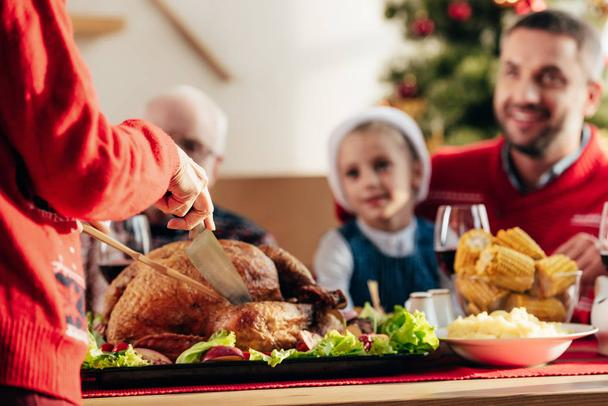 cropped image of woman slicing delicious tukey for christmas dinner with happy family at home - Photo, Image