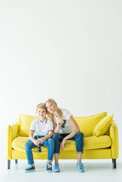 smiling mother and son holding bottles of soda and sitting on yellow sofa - Photo, Image