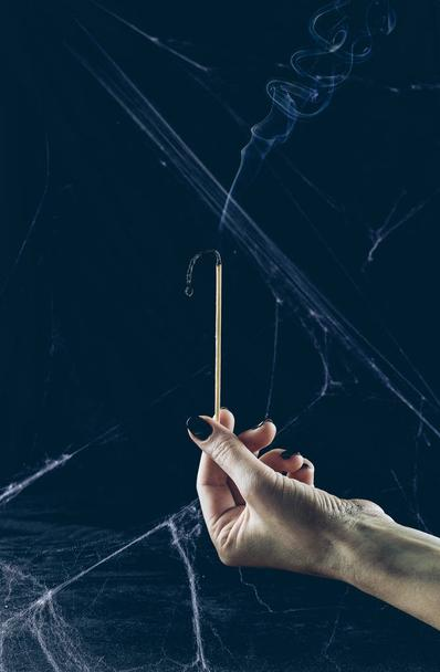 partial view of gloomy woman holding big match with smoke in darkness with spider web - Photo, Image