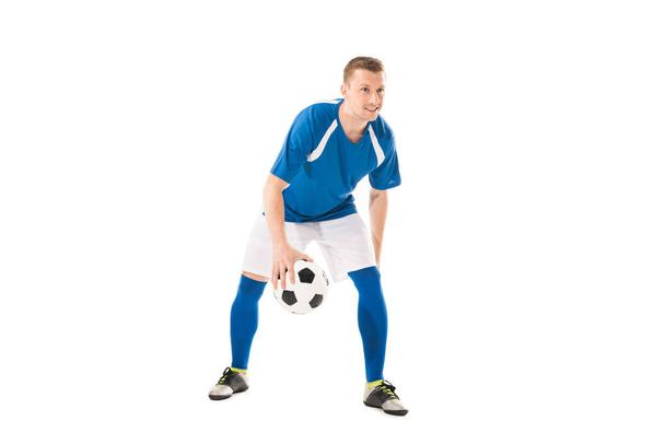 full length view of smiling young sportsman playing with soccer ball isolated on white - Photo, Image
