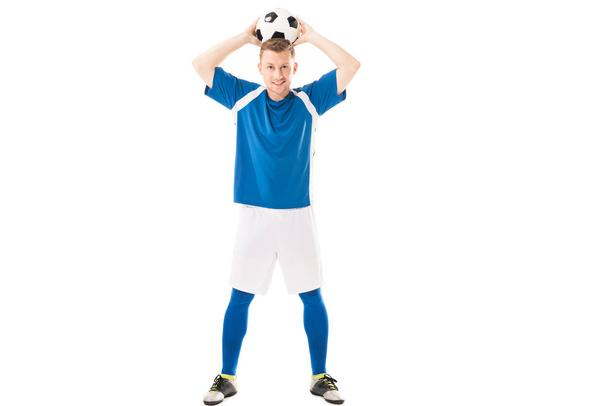 full length view of happy young soccer player holding ball above head and smiling at camera isolated on white - Photo, Image