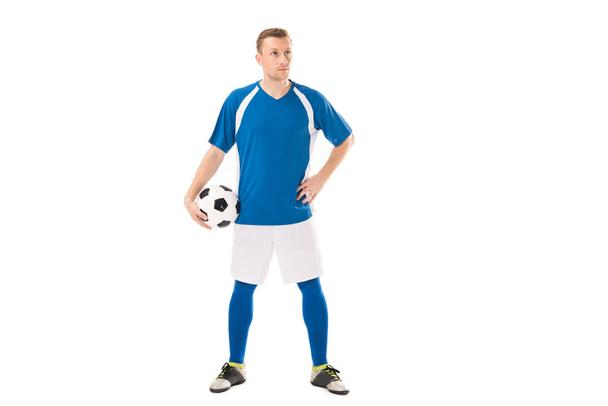 confident young soccer player holding ball and looking away isolated on white - Photo, Image
