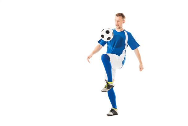 full length view of athletic young sportsman in soccer uniform training with ball isolated on white  - Photo, Image