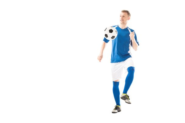 full length view of smiling young sportsman playing with soccer ball and looking away isolated on white - Photo, Image