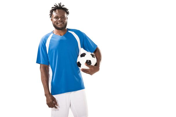 handsome african american soccer player holding ball and smiling at camera isolated on white - Photo, Image