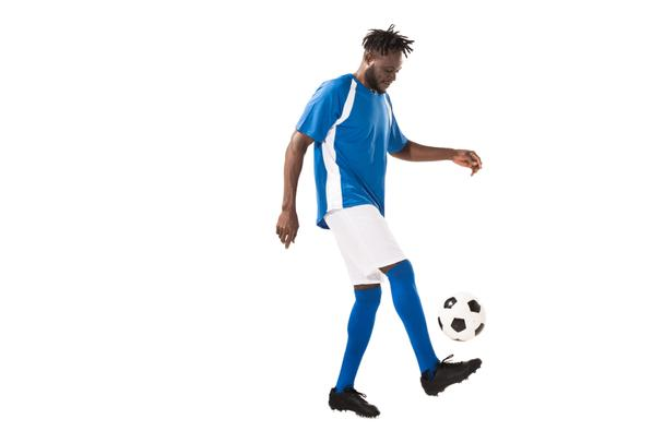 side view of athletic african american sportsman playing with soccer ball isolated on white  - Photo, Image