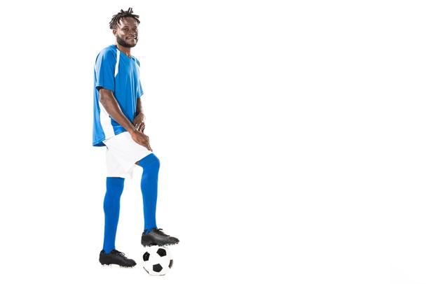full length view of athletic african american sportsman standing with soccer ball and smiling at camera isolated on white - Photo, Image