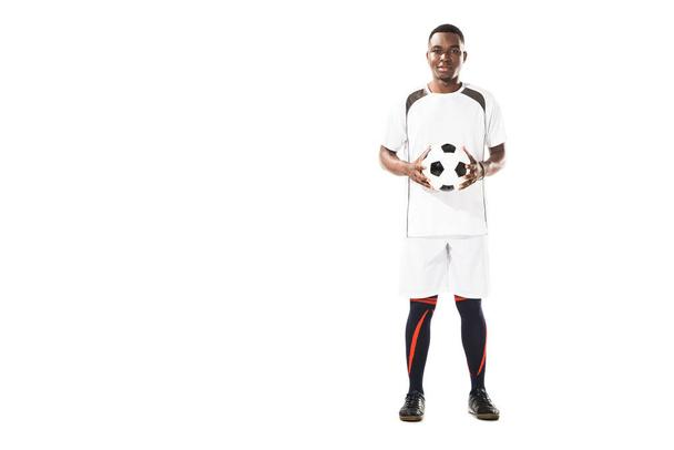 full length view of happy young african american soccer player holding ball and smiling at camera isolated on white - Photo, Image