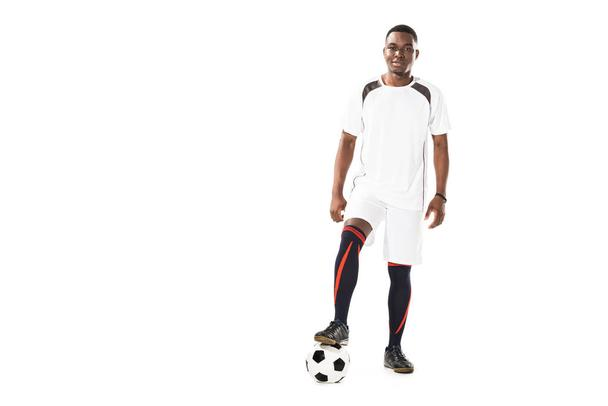 handsome young african american sportsman standing with soccer ball and smiling at camera isolated on white - Photo, Image