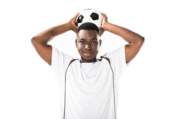 young african american soccer player holding ball above head and smiling at camera isolated on white  - Photo, Image
