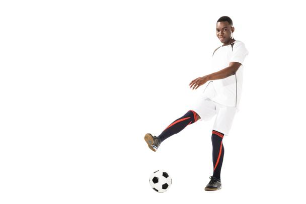 young african american soccer player kicking ball and smiling at camera isolated on white - Photo, Image