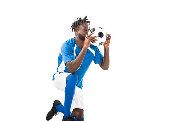 african american sportsman kneeling and holding soccer ball isolated on white - Photo, Image