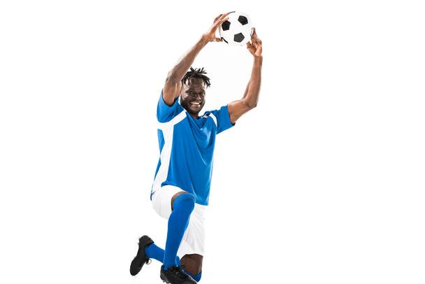 happy african american soccer player holding ball above head and smiling at camera isolated on white - Photo, Image